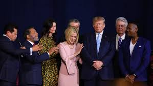 Trump goes through the motions of prayer with evanglist Paula White.